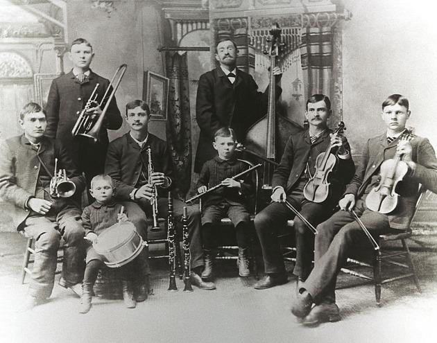Es ist ein uraltes schwarzweißes Foto. Auf dem Bild ist eine Musik-Band abgebildet. Vorne sitzen sechs Kinder, alle mit einem Musikinstrument und in verschiedenem Alter. Im Hintergrund steht noch ein Bub links, in der Bildmitte steht ein älterer Mann mit